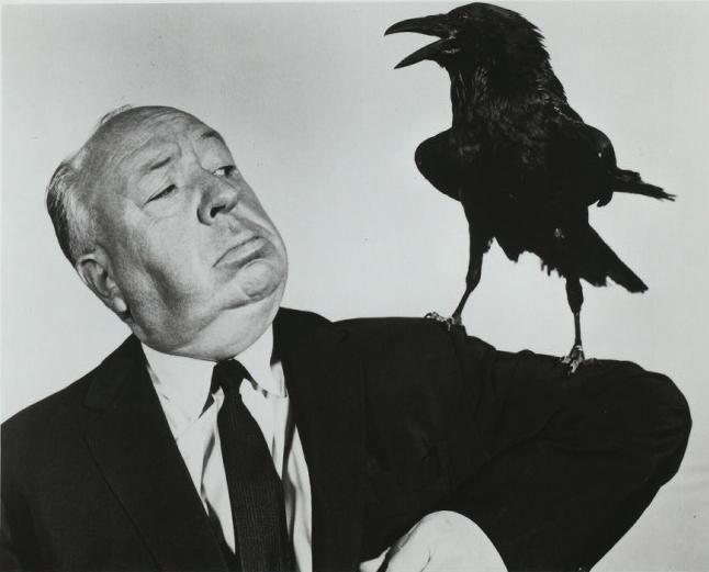 Photo noir et blanc d'Alfred Hitchcock tenant un corbeau sur son bras