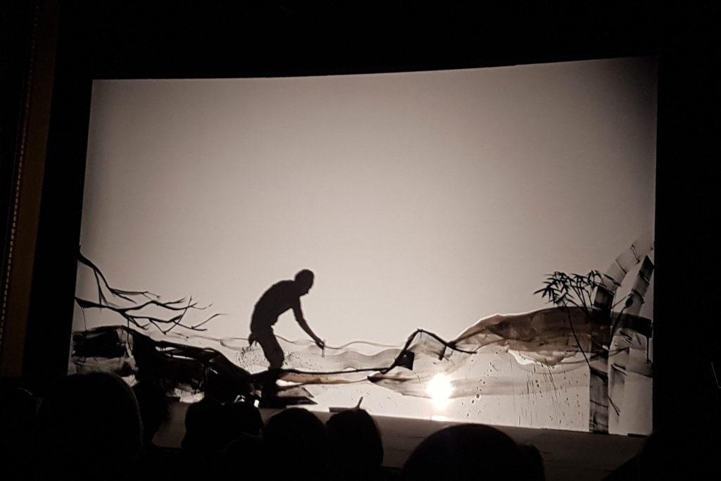 Silhouette du dessinateur qui s'affiche par dessus le paysage derrière l'écran