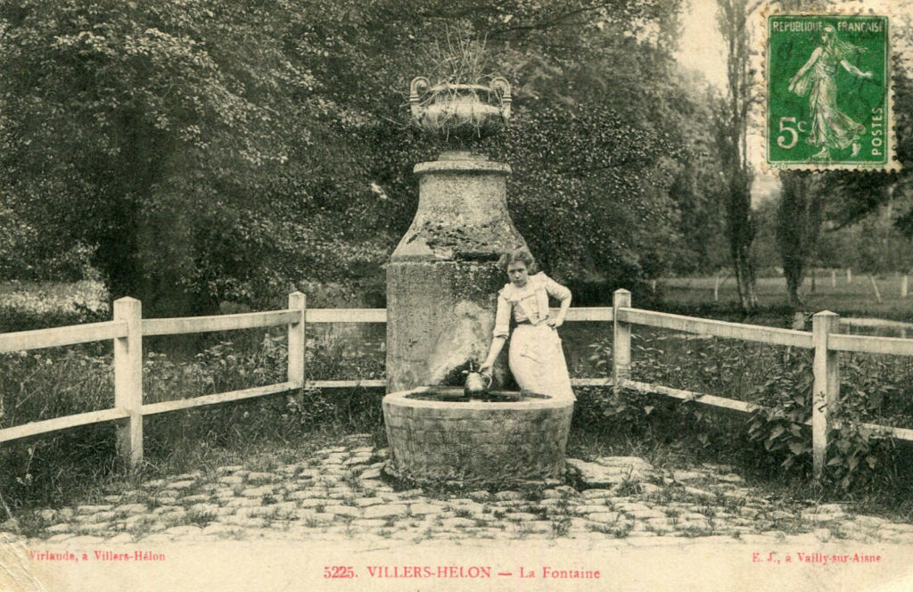 Carte postale en noir et blanc : femme à la corvée d'eau à la fontaine